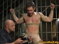BDSM sub restrained in cell and jerked by cop
